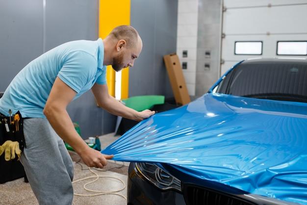 L'involucro per auto maschile mette un foglio di vinile protettivo o una pellicola sul cofano. il lavoratore fa i dettagli automatici. rivestimento protettivo per vernice automobilistica, messa a punto professionale