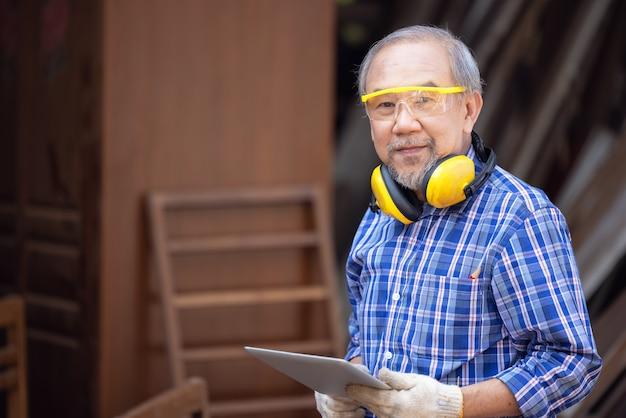 Falegname maschio in un laboratorio di costruzione, utilizzando una tavoletta digitale