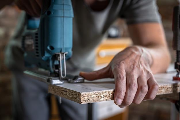 Un falegname maschio taglia un legno con un seghetto alternativo elettrico, lavorando con un albero.