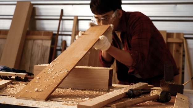 Carpentiere maschio che tiene e che controlla pezzo di bordo nel sito.