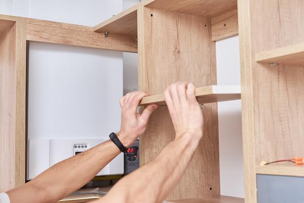 Il carpentiere maschio installa la mensola nell'armadio della cucina