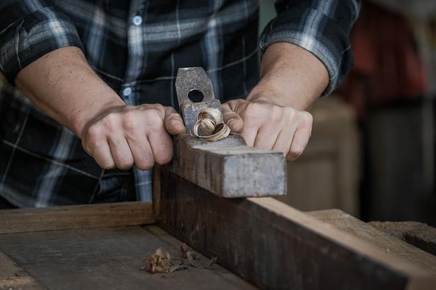 Un falegname maschio sta usando una pialla per raschiare la superficie in legno.