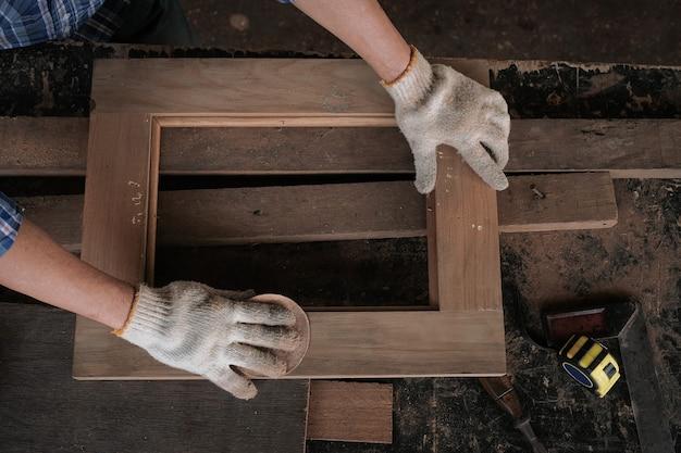 Il falegname maschio usa la carta vetrata per lucidare la lavorazione del legno.