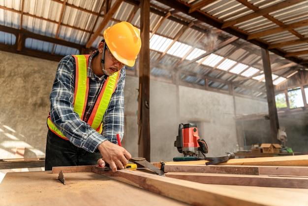 Un carpentiere maschio che usa la matita su un pezzo di legno in cantiere
