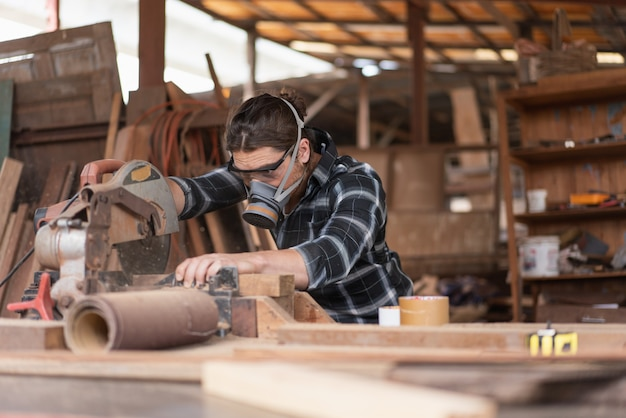 Il falegname maschio indossa una maschera per evitare che i trucioli di legno gli entrino in faccia mentre utilizza una sega circolare per tagliare la lavorazione del legno in un laboratorio di falegnameria.
