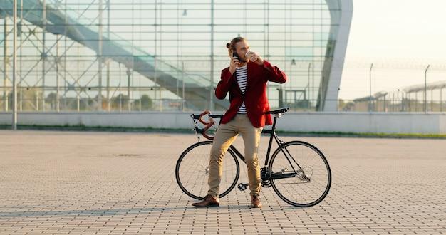 Cavaliere di bici bello casual maschio in giacca rossa che si siede sulla bicicletta, sorseggiando una bevanda calda e parlando al cellulare. in un grande edificio moderno in vetro. uomo caucasico che beve caffè. e parlando al cellulare.
