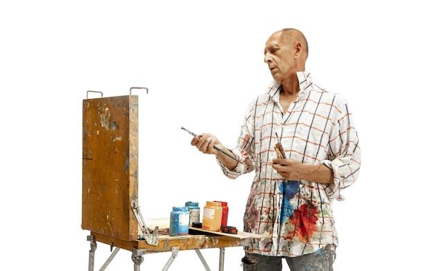 Artista caucasico maschio al lavoro isolato su bianco