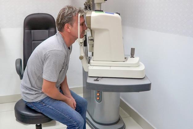 Il maschio controlla la sua visione sulla macchina controllando la visione del paziente presso la clinica oculistica o il negozio di ottica.