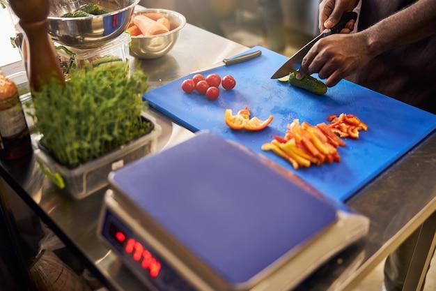 Chef maschio in grembiule in piedi all'interno del ristorante e preparare le verdure per il piatto