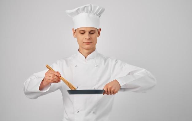Cuoco unico maschio che cucina l'uniforme professionale del servizio del ristorante
