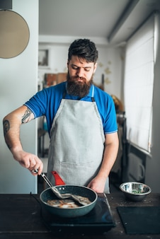 Cuoco unico maschio che cucina il filetto di pesce della spigola su una padella. preparazione di frutti di mare