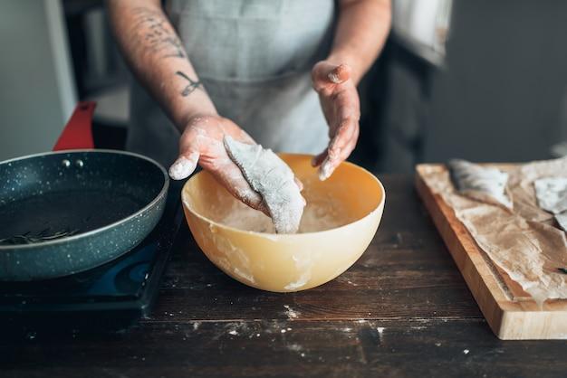 Mani maschii del cuoco unico che cucinano pesce su una padella. cucina alimentare. preparazione di frutti di mare