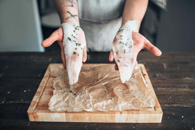 Le mani maschii dello chef tiene le fette di pesce crudo con le spezie sopra la vista del primo piano del tagliere di legno. cucina di pesce. preparazione di frutti di mare freschi