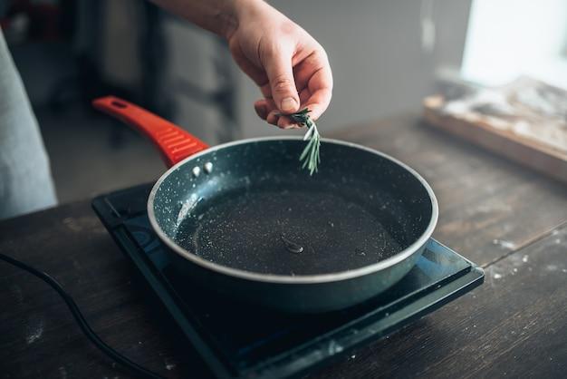Mani maschii dello chef mette il rosmarino in una padella antiaderente. cucina alimentare. preparazione di pesce e frutti di mare