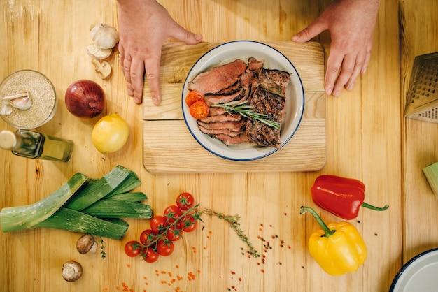 Mani di chef maschio e fette di carne arrosto in un piatto