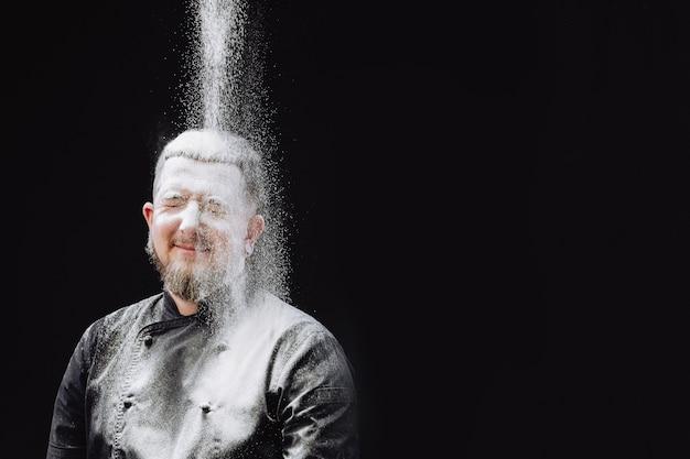 Cuoco unico maschio che produce pasta in cucina. lo chef viene inondato di farina. felice fornaio.