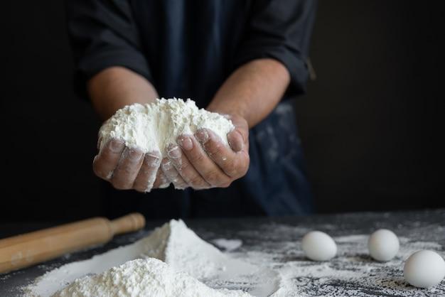 Il cuoco unico maschio, le mani maschii stanno tenendo una grande manciata di farina su una tavola nera. concetto di panetteria