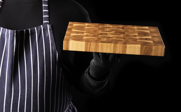 Chef maschio in un grembiule blu a strisce e vestiti neri si erge su uno sfondo nero e tiene in mano un tagliere da cucina rettangolare in legno, primi piani