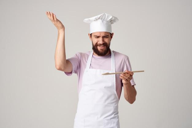Chef maschio in uniforme che cucina cucina professionale