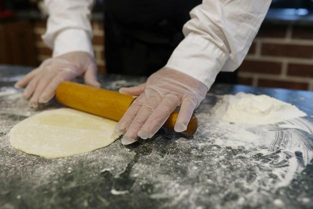 Lo chef maschio usa gli ingredienti per preparare i prodotti a base di farina sul tavolo della cucina