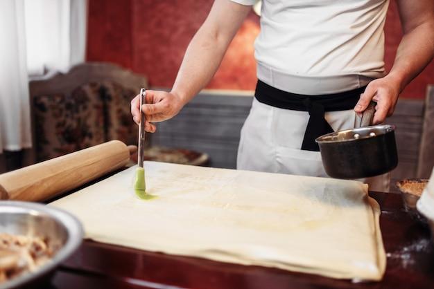 Cuoco unico maschio in grembiule bianco che cucina lo strudel di mele sulla cucina. dessert dolce fatto in casa, processo di preparazione