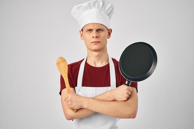 Cuoco unico maschio in una padella bianca del grembiule in mano che cucina il cibo