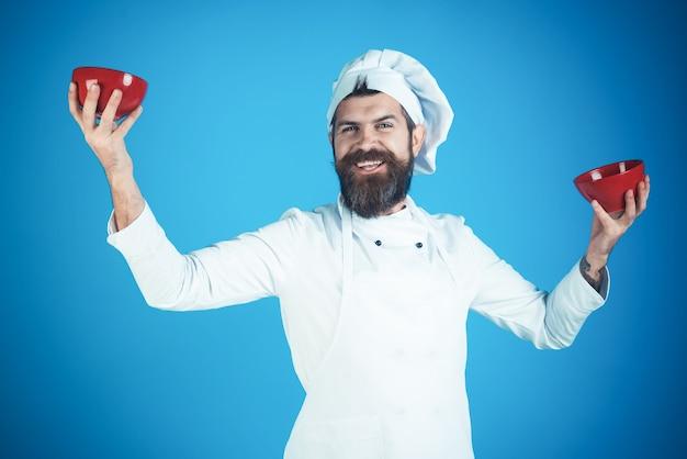 Lo chef maschio in uniforme bianca tiene in mano ciotole rosse chef barbuto isolato su concetto di cucina bluebackground
