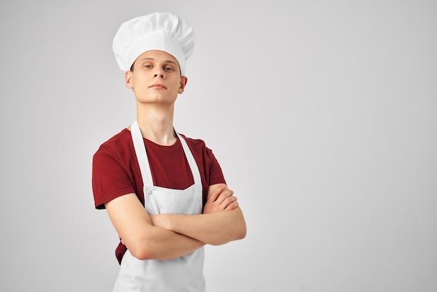 Chef maschio con un berretto in testa professionisti della cucina sfondo chiaro