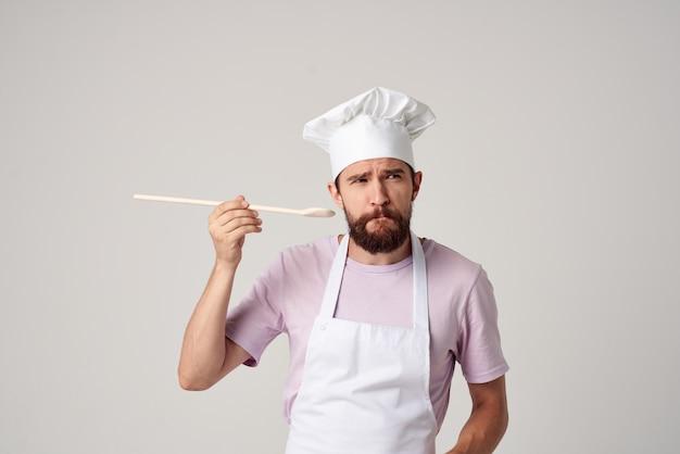 Chef maschio con un berretto in testa che assaggia cucina professionale