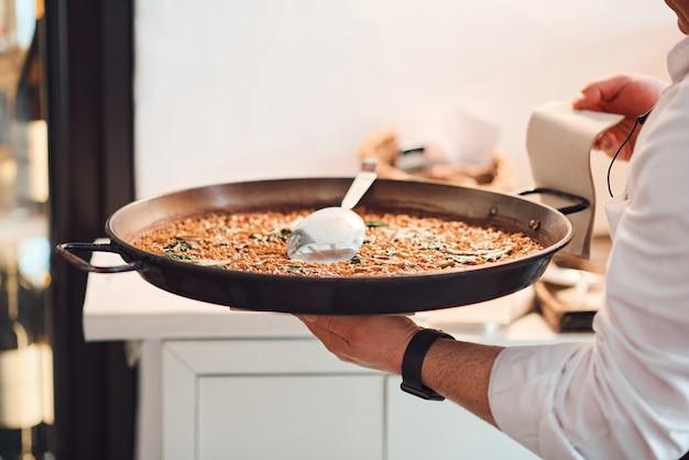 Chef maschio con un piatto di paella nelle sue mani