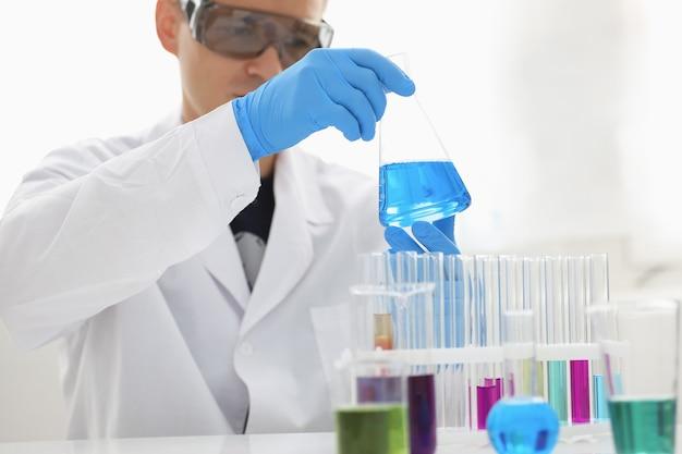 Un chimico maschio tiene la provetta di vetro nella sua mano trabocca una soluzione liquida di permanganato di potassio conduce una reazione di analisi