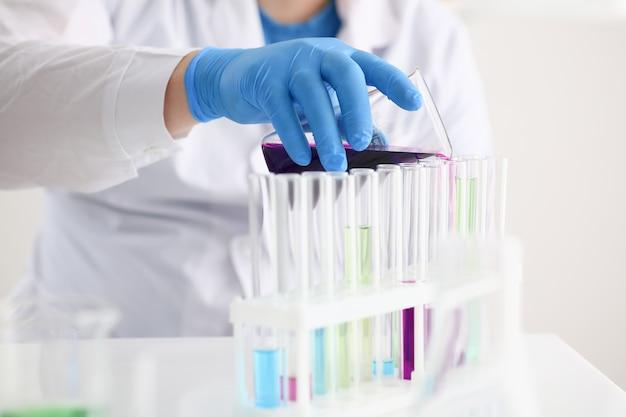 Un chimico maschio tiene la provetta di vetro nella sua mano trabocca una soluzione liquida