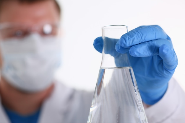 Un chimico maschio tiene in mano una provetta di vetro che trabocca un liquido