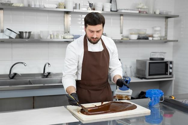 Il cioccolatiere maschio utilizza una spatola per mescolare il cioccolato liquido temperato su un tavolo di granito
