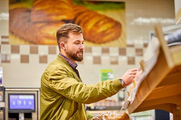 Maschio che sceglie il pane nel supermercato, bel ragazzo in maglione guarda panetteria fresca in negozio, vuole comprarlo