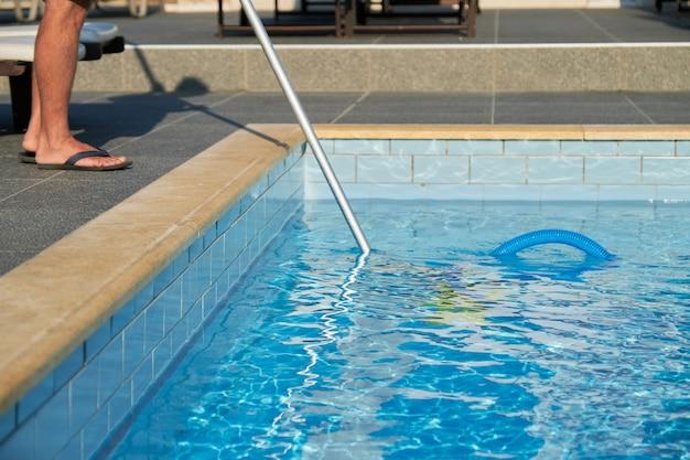 Piscina all'aperto di pulizia maschile con tubo a vuoto subacqueo.