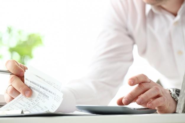 Il dito maschio dell'impiegato che preme i bottoni sul calcolatore escogita la valutazione delle spese