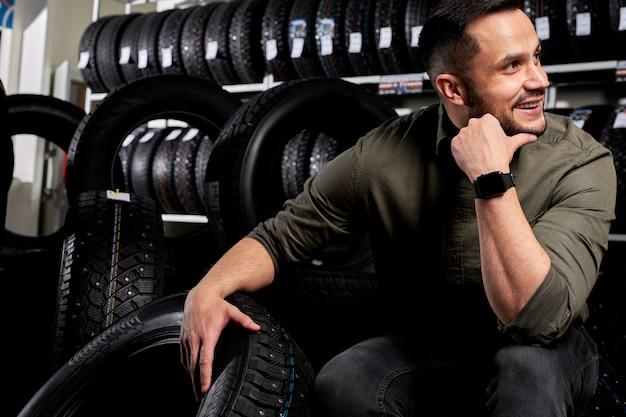 Il cliente maschio nel servizio auto si siede pensando, guardando di lato e sorridendo, scegli il miglior pneumatico per auto. automobili, automobile, concetto di veicolo