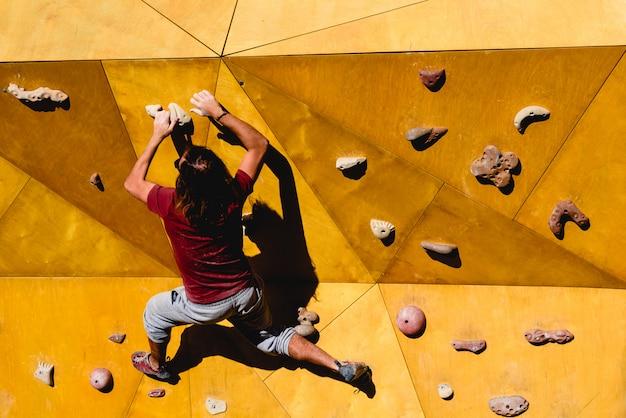 Scalatore maschio che prova un percorso complicato verso il sole su una parete da arrampicata all'aperto