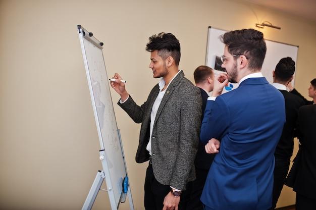 I colleghi maschi che lavorano in gruppo collaborano, l'equipaggio multirazziale di dipendenti si è concentrato sulla pianificazione del progetto contro la lavagna a fogli mobili e discutendo idee.