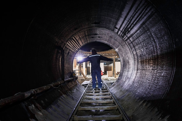 Tunnel sotterraneo confinato maschile del condotto di riscaldamento con tubi e rotaia arrugginiti