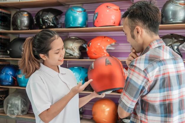 Il consumatore maschio sceglie i caschi quando viene servito da negozianti nei negozi di caschi