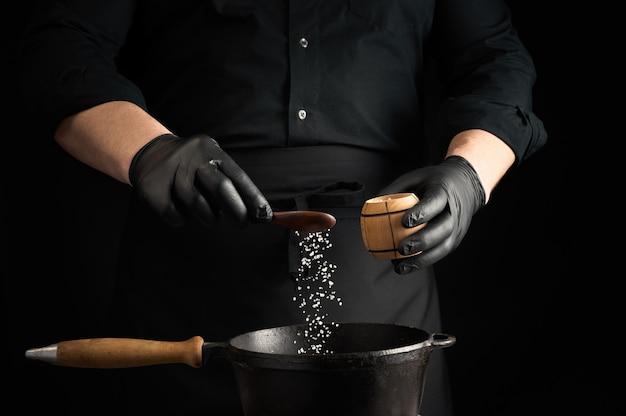 Il cuoco maschio in uniforme nera e guanti di lattice salano il cibo in una padella di ghisa nera, i cristalli di sale si congelano nell'aria