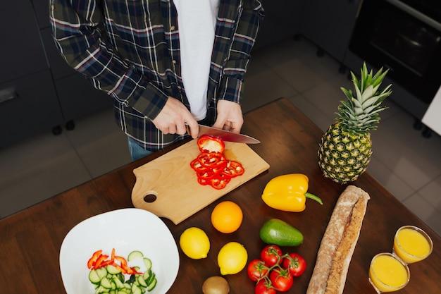 Cuoco maschio che taglia pepe rosso sul bordo di legno in cucina