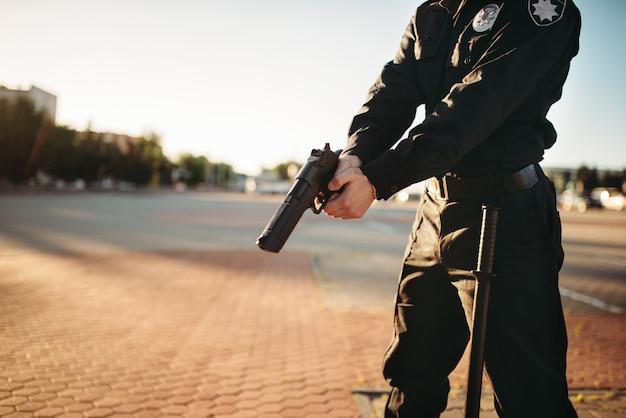 Poliziotto maschio in uniforme con la pistola in mano