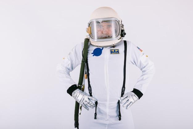 Cosmonauta maschio in tuta spaziale e casco, mani sulla vita, su sfondo bianco.