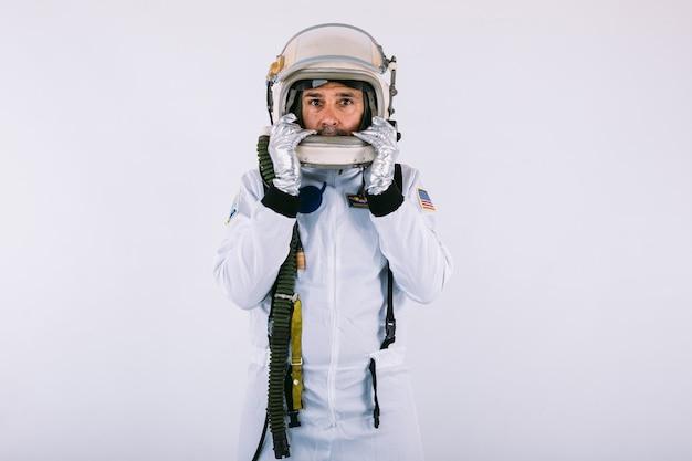 Cosmonauta maschio in tuta spaziale e casco tenendo il casco con le mani su sfondo bianco