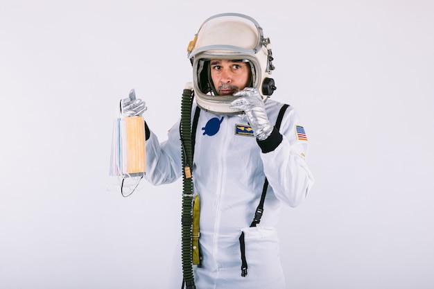 Cosmonauta maschio in tuta spaziale e casco, con in mano molte maschere chirurgiche colorate a forma di ventaglio, su sfondo bianco. covid-19 e concetto di virus