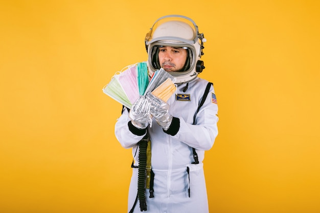 Cosmonauta maschio in tuta spaziale e casco, con in mano molte maschere chirurgiche colorate a forma di ventaglio, sulla parete gialla. covid19 e il concetto di virus