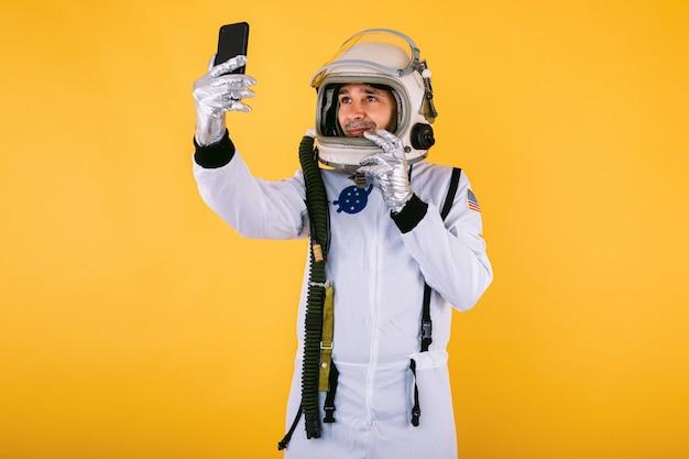 Cosmonauta maschio in tuta spaziale e casco, prendendo un selfie con il cellulare, sulla parete gialla.